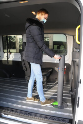 Frau die in einem Transporter einen Desinfektionsspender nutzt
