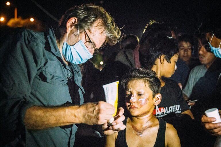 mann mit brille und mundschutz der einer frau mit gesichtsverletzungen hilft