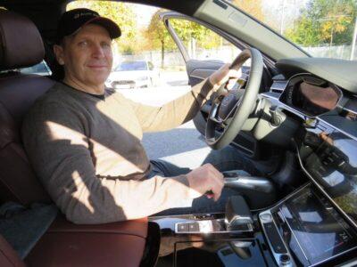Mann mit Kappe hinter dem Lenkrad eines Autos