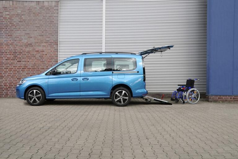 Blauer VW Caddy von der Seite mit geöffneter Heckklappe und Rollstuhl