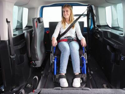 Junge Frau im Rollstuhl im neuen VW Caddy