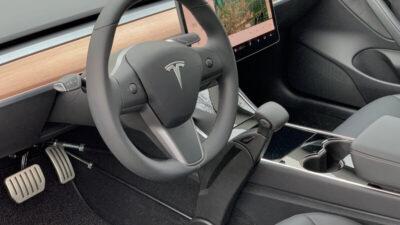 Blick aufs Cockpit eines Tesla mit Lenkrad und Handbedienung für Menschen mit Behinderung