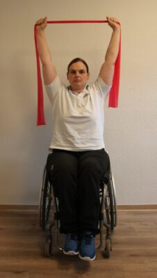 Rollstuhlfahrerin mit Armen über dem Kopf und Fitnessband bei einer Übung