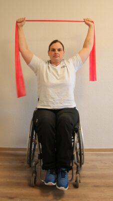 Rollstuhlfahrerin mit Armen nach oben und Fitnessband bei einer Übung
