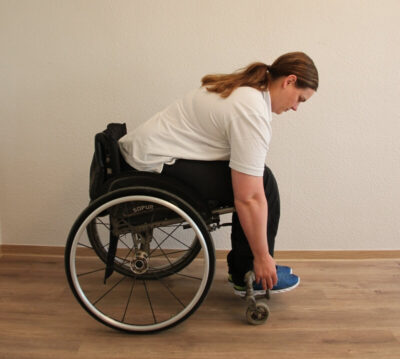 Rollstuhlfahrerin bei einer Fitnessübung nach vorne gebeugt