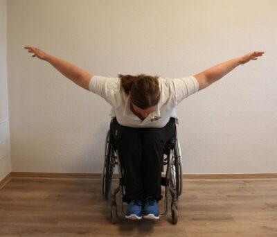 Rollstuhlfahrer bei einer Fitnessübung nach vorne gebeugt mit ausgebreiteten Armen