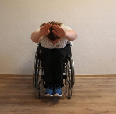 Rollstuhlfahrer bei einer Fitnessübung nach vorne gebeugt mit nach vorne ausgestreckten Armen