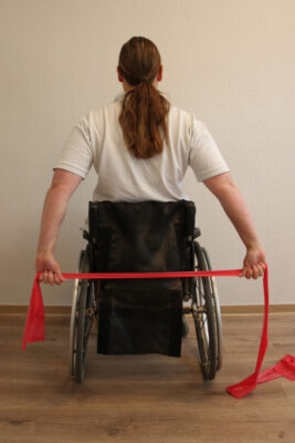 Rollstuhlfahrerin mit Fitnessband bei einer Übung