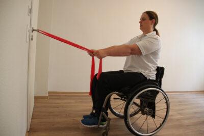Rollstuhlfahrerin mit Fitnessband bei einer Sportübung