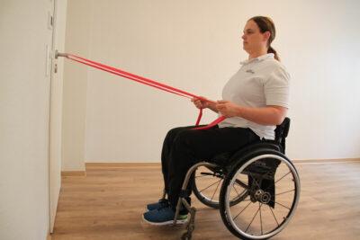 Rollstuhlfahrerin mit Fitnessband bei einer Übung an einer Tür