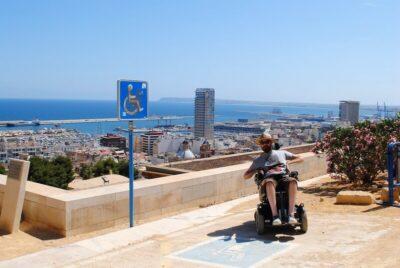 Rollstuhlfahrer im Urlaub vor einer Skyline