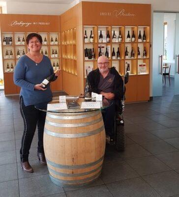 Mann im Rollstuhl neben einem Weinfass