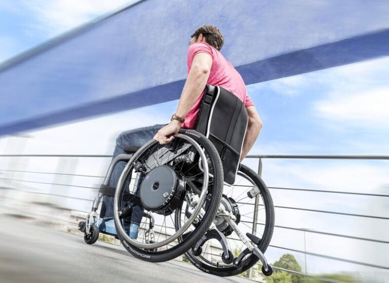 Rollstuhlfahrer von hinten der bergan fährt