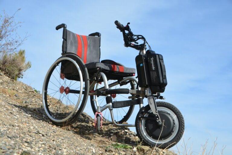 Rollstuhl mit Rollstuhlzuggerät an einem Berg