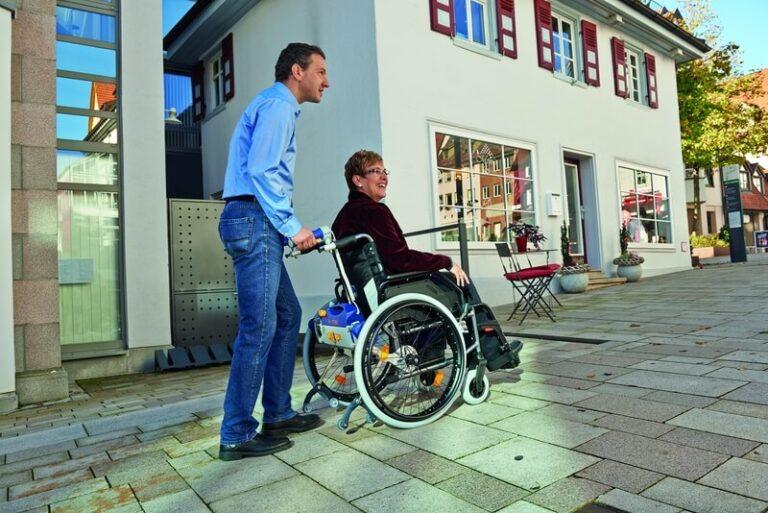 Mann der in der Stadt einen Rollstuhlfahrer schiebt