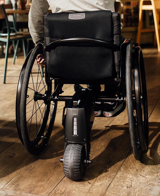 Rollstuhl von hinten mit einem elektrischen Zusatzantrieb