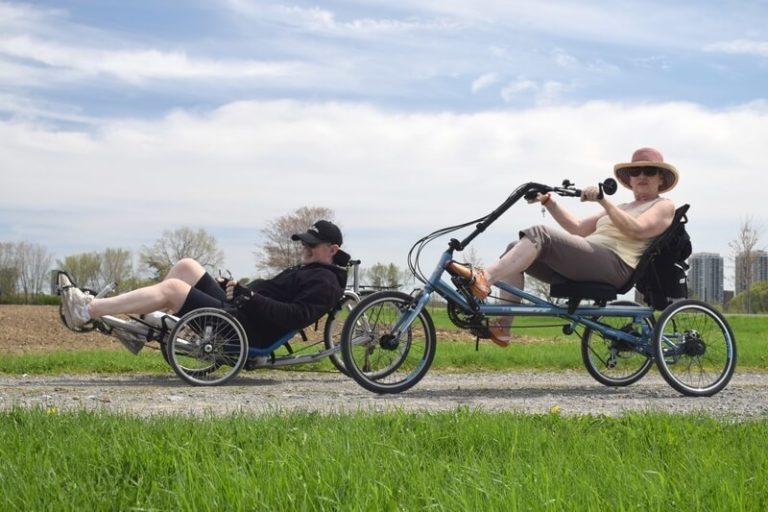 Zwei ältere Menschen seitlich von unten auf Spezailfahrrädern fotografiert