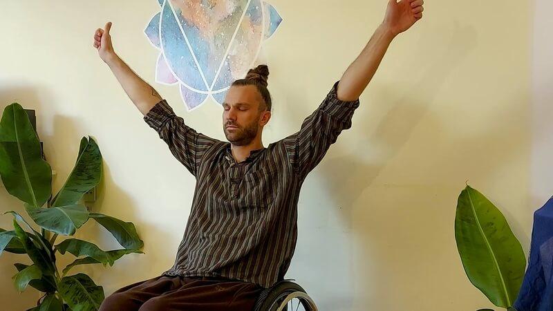 Mann im rollstuhl bei einer Yoga-Übung