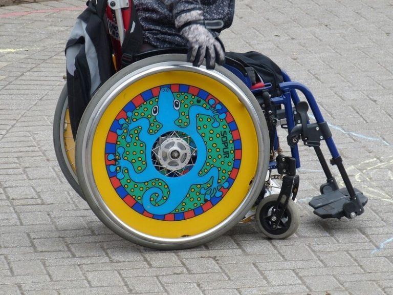 Bild von der Seite auf einen Rollstuhl mit Kind