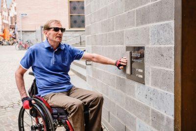 Blinder Rollstuhlfahrer an einem Klingelschild
