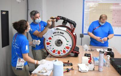 Drei Menschen reparieren in einer Werkstatt einen Rollstuhl