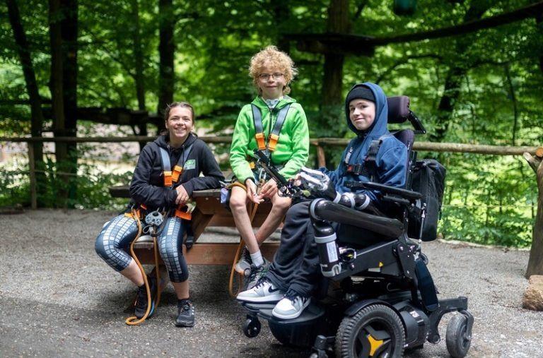 Junger Elektrorollstuhlfahrer und zwei Kletterer auf einer Bank im Wald